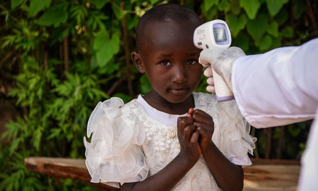 Membro da equipe do Ministério da Saúde mede a temperatura de uma menina durante o testes em motoristas e passageiros na rodovia em Nakuru, Quênia. País registrou 50 casos de Covid-19 e uma morte Foto: SULEIMAN MBATIAH / AFP