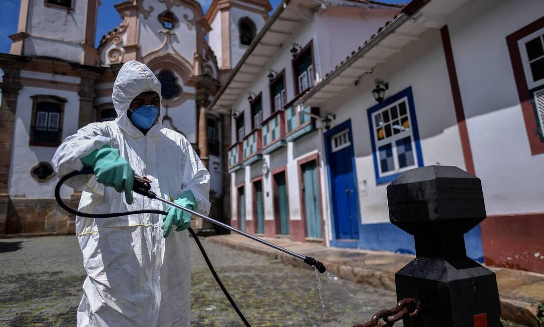 Membro de uma equipe de limpeza desinfeta as ruas ao redor da Basílica de Nossa Senhora do Pilar, em Ouro Preto, Minas Gerais, Brasil Foto: DOUGLAS MAGNO / AFP
