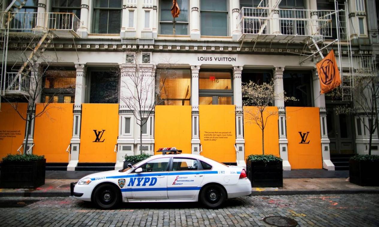 Carro da polícia de Nova York está estacionado em frente a uma loja Louis Vuitton coberta com janelas e entradas de compensado para evitar saques durante surto da Covid-19 Foto: EDUARDO MUNOZ / REUTERS