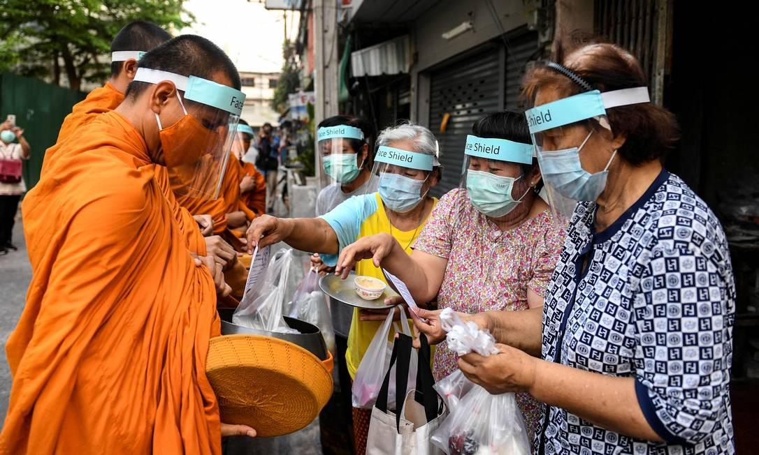 Monges budistas usam escudos e máscaras para se proteger da Covid-19 enquanto coletam esmolas em Bangkok, Tailândia Foto: CHALINEE THIRASUPA / REUTERS