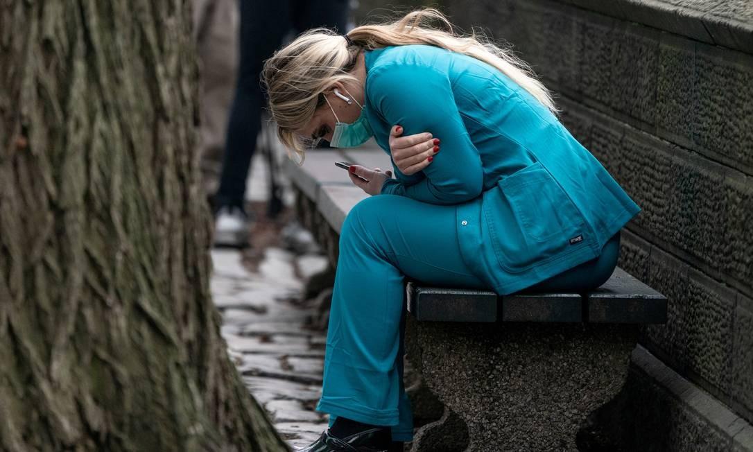 Um profissional de saúde está sentado em um banco perto do Central Park, no bairro de Manhattan, em Nova York Foto: JEENAH MOON / REUTERS