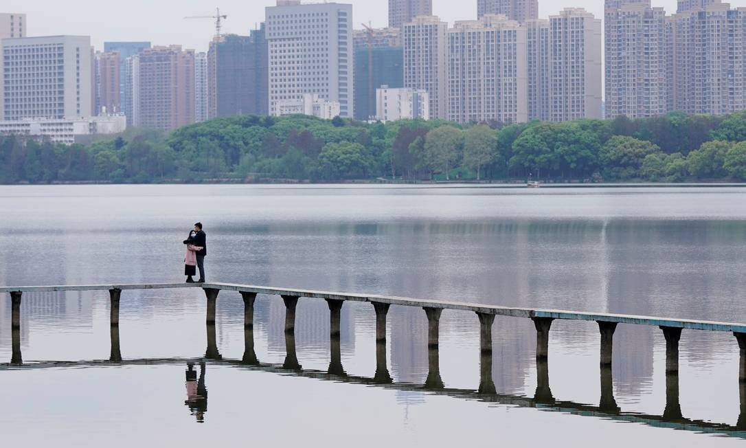 Pessoas usam máscaras e se abraçam no East Lake em Wuhan, província de Hubei, na China Foto: ALY SONG / REUTERS