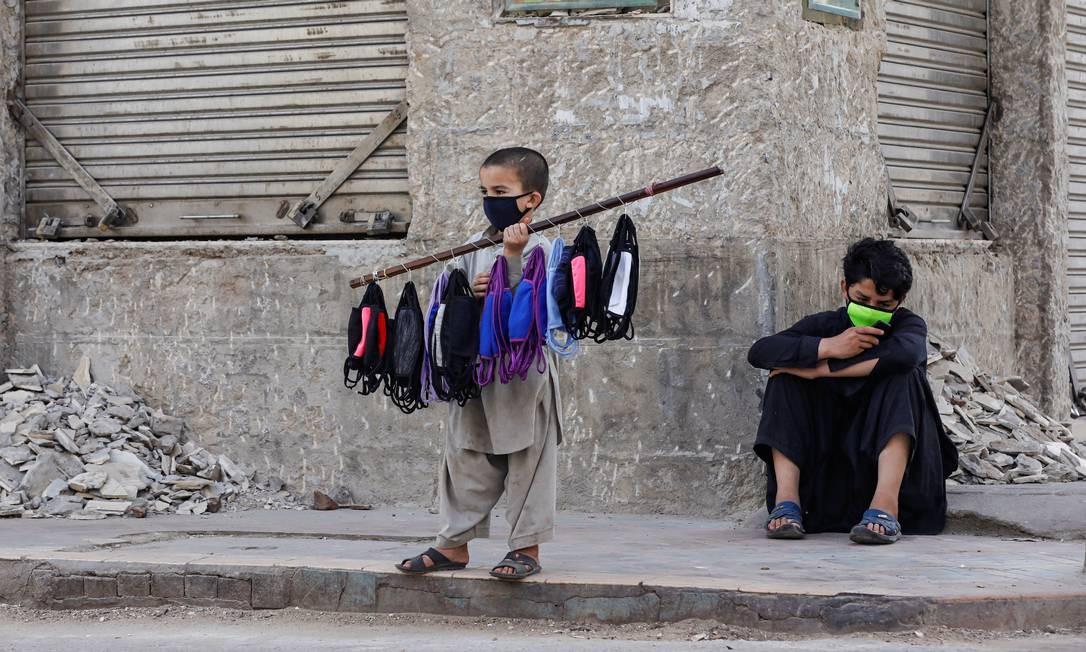 Menino de 7 anos vende máscaras com o irmão na esquina de uma rua durante um bloqueio depois que o Paquistão fechou todos os mercados, locais públicos e desencorajou grandes reuniões em meio a um surto do novo coronavírus, em Karachi Foto: AKHTAR SOOMRO / REUTERS