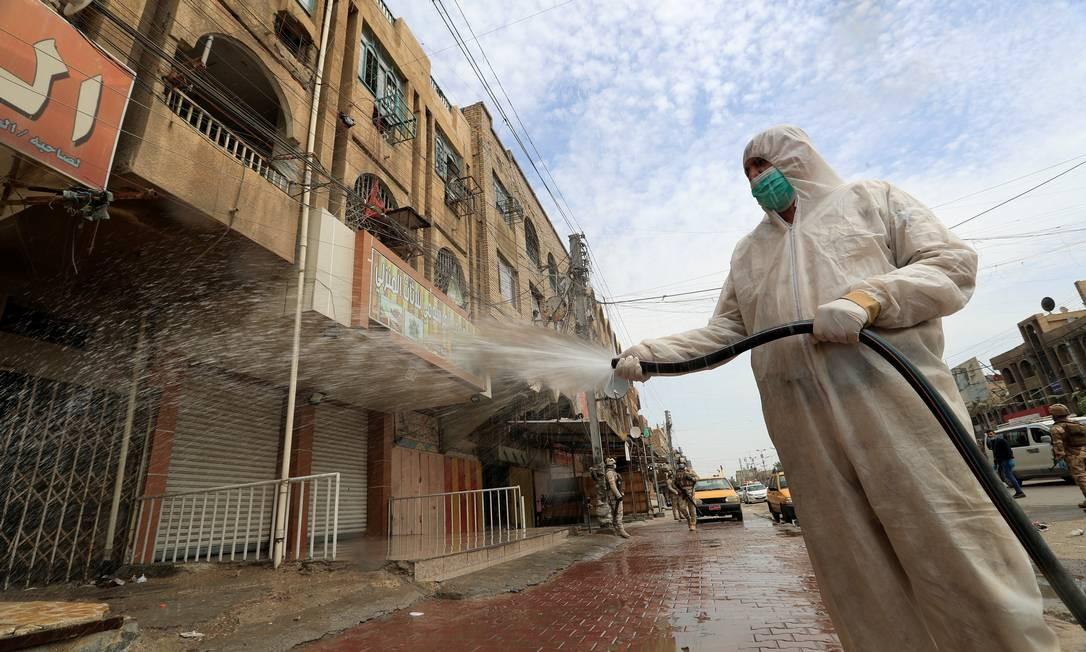 Soldado iraquiano vestindo um traje de proteção pulveriza desinfetante para higienizar uma rua, durante um toque de recolher imposto para impedir a propagação da Covid-19, em Bagdá, Iraque Foto: THAIER AL-SUDANI / REUTERS