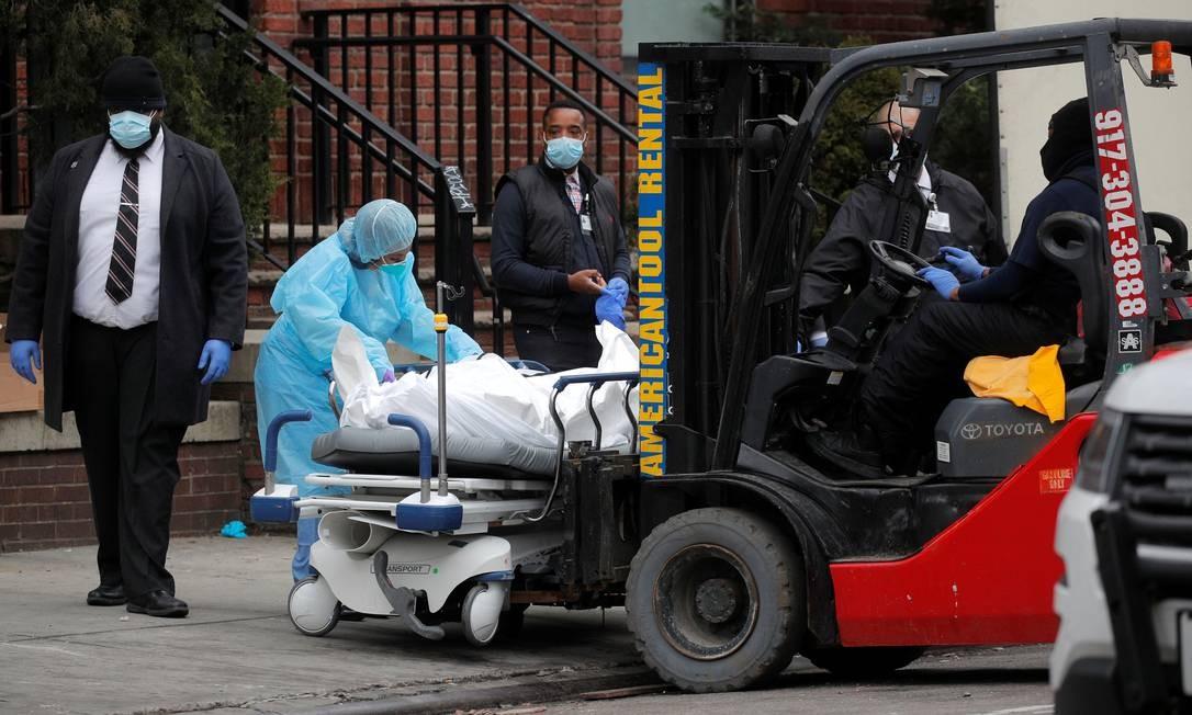 Trabalhadores se preparam para carregar uma pessoa falecida em uma empilhadeira fora do Brooklyn Hospital Center, no bairro de Brooklyn em Nova York Foto: BRENDAN MCDERMID / REUTERS
