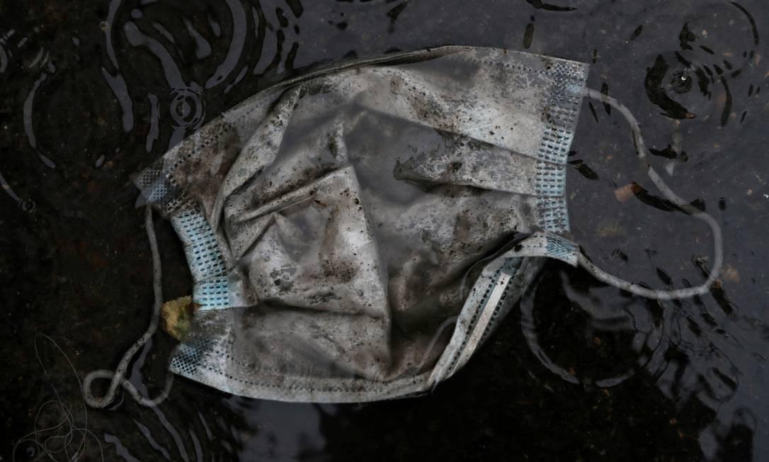 Uma máscara protetora é vista na chuva em uma rua deserta, durante o surto da doença em Madri, Espanha Foto: SUSANA VERA / REUTERS