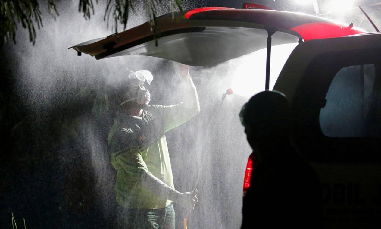 Trabalhador municipal pulveriza com desinfetante uma ambulância carregando o caixão de uma vítima da Covid-19, em Jacarta, na Indonésia Foto: WILLY KURNIAWAN / REUTERS
