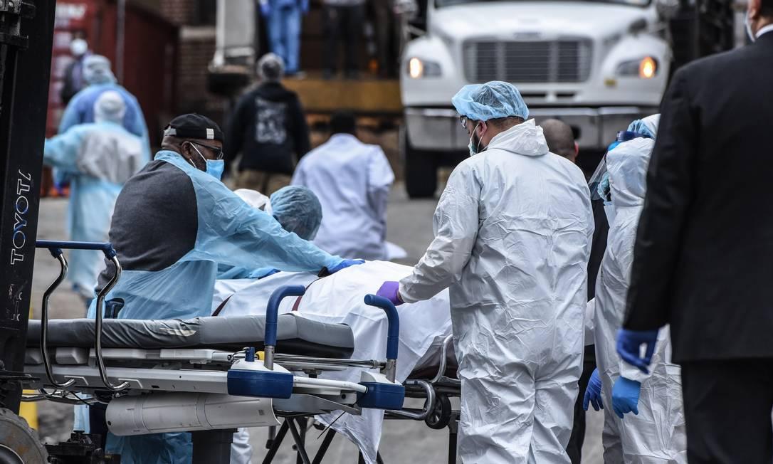 Profissionais da saúde usam roupa protetora para remover corpo de vítima do coronavírus, no Brookyln, em Nova York Foto: STEPHANIE KEITH / AFP