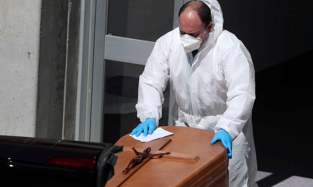 Agente funerário carrega caixão de pessoa morta pelo Covid-19 Foto: SUSANA VERA/Reuters