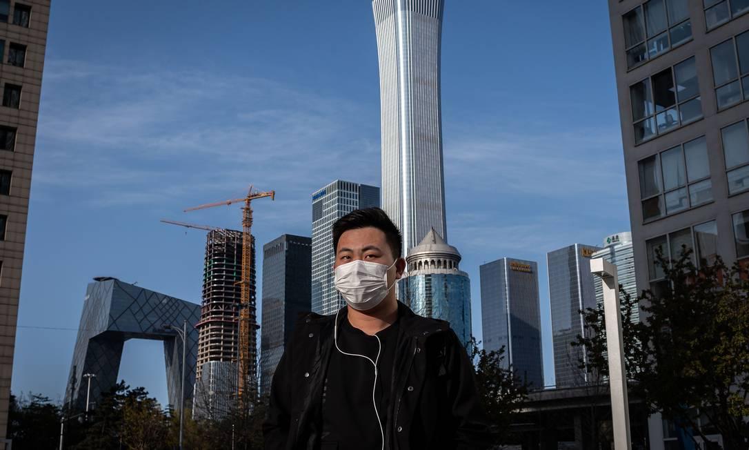 Homem caminha em distrito comercial de Pequim, na China, com máscara nesta quarta-feira (1) Foto: NICOLAS ASFOURI / AFP