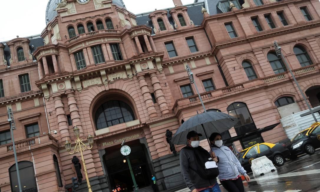 Casal usando máscaras atravessa a rua em frente à Casa Rosada, sede do governo argentino Foto: Agustin Marcarian / Reuters