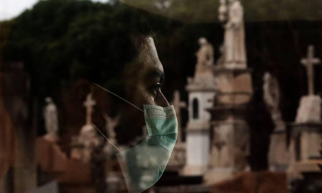 Imagem de um homem com máscara protetora refletida no vidro de uma das capelas do Cemitério São Francisco Xavier. Medidas de proteção estão sendo adotadas durante funerais em meio à pandemia Foto: FABIO MOTTA / Agência O Globo