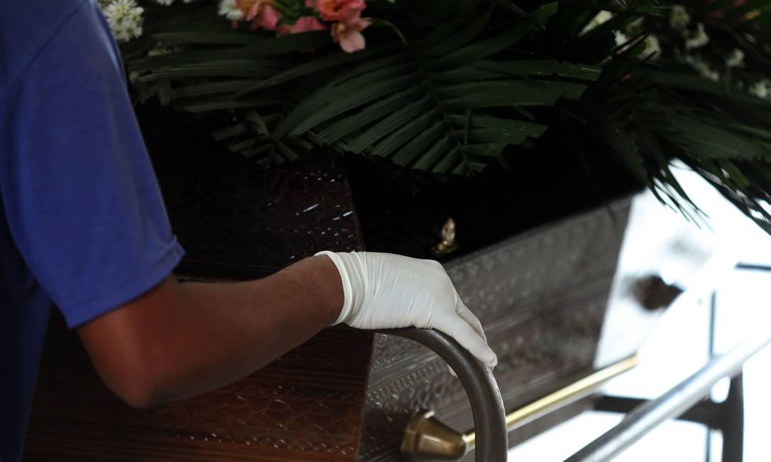 Funcionário usa luvas enquanto empurra um caixão no São Francisco Xavier Foto: FABIO MOTTA / Agência O Globo
