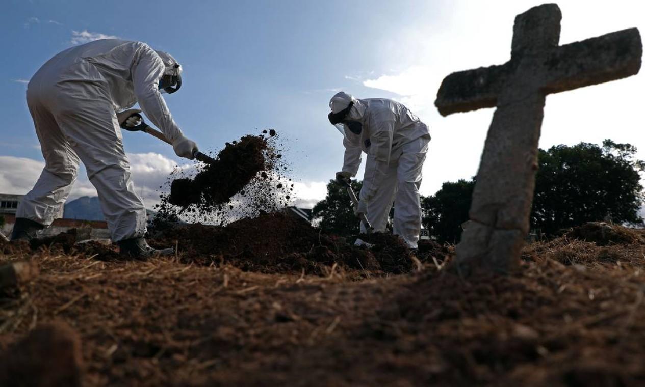 Funcionários usam traje de proteção enquanto fazem o enterro de Nazareno Rodrigues Costa, de 72 anos, em 1º de abril de 2020, no Cemitério São Francisco Xavier no Caju, Zona Portuária do Rio. Idoso morreu com suspeita de Covid-19 Foto: FABIO MOTTA / Agência O Globo
