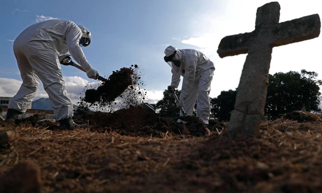 Funcionários usam traje de proteção enquanto fazem o enterro de Nazareno Rodrigues Costa, de 72 anos, no Cemitério São Francisco Xavier no Caju, Zona Portuária do Rio. Idoso morreu na segunda-feira, com suspeita de Covid-19 Foto: FABIO MOTTA / Agência O Globo