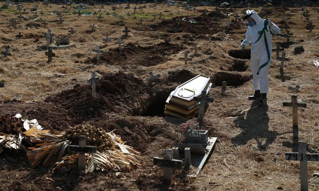 Enterro de Nazareno Rodrigues Costa, 72 anos, no Cemitério do Caju. Funcionários utilizam roupa especial para evitar contágio da doença Foto: FABIO MOTTA / Agência O Globo