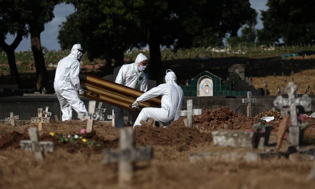 Por causa da pandemia de Covid-19, medidas de segurança estão sendo adotadas não só pelos funcionários dos cemitérios, como também por familiares e demais enlutados, que passaram a usar máscaras durante os funerais Foto: FABIO MOTTA / Agência O Globo