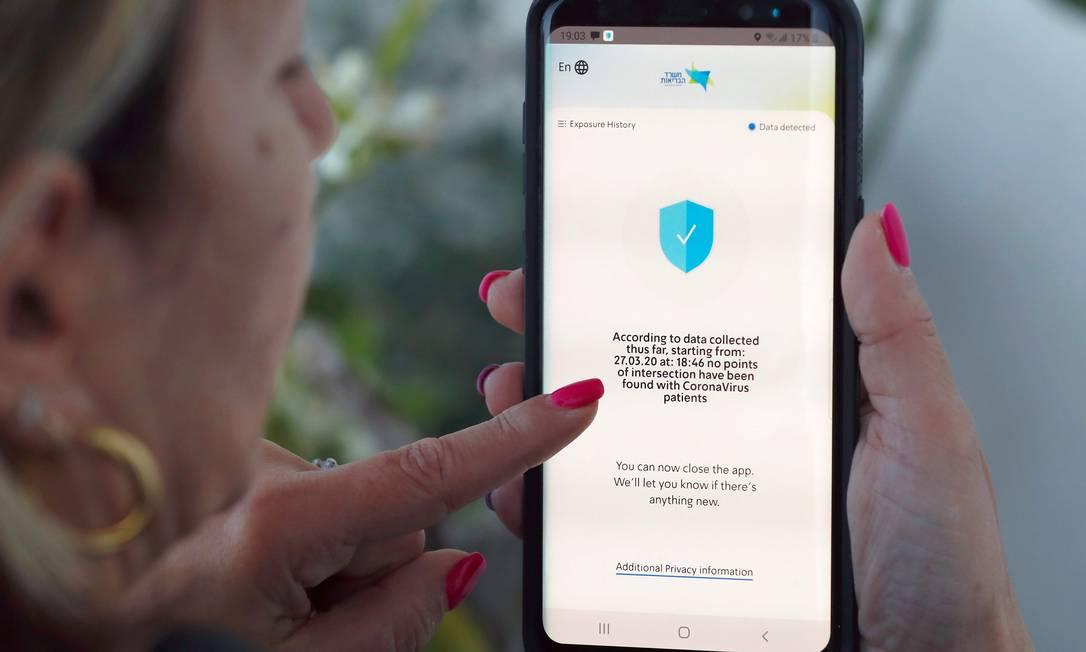 Mulher israelense checa em seu smartphone o aplicativo HaMagen, que monitora casos de coronavírus no país Foto: JACK GUEZ / AFP/29-03-2020