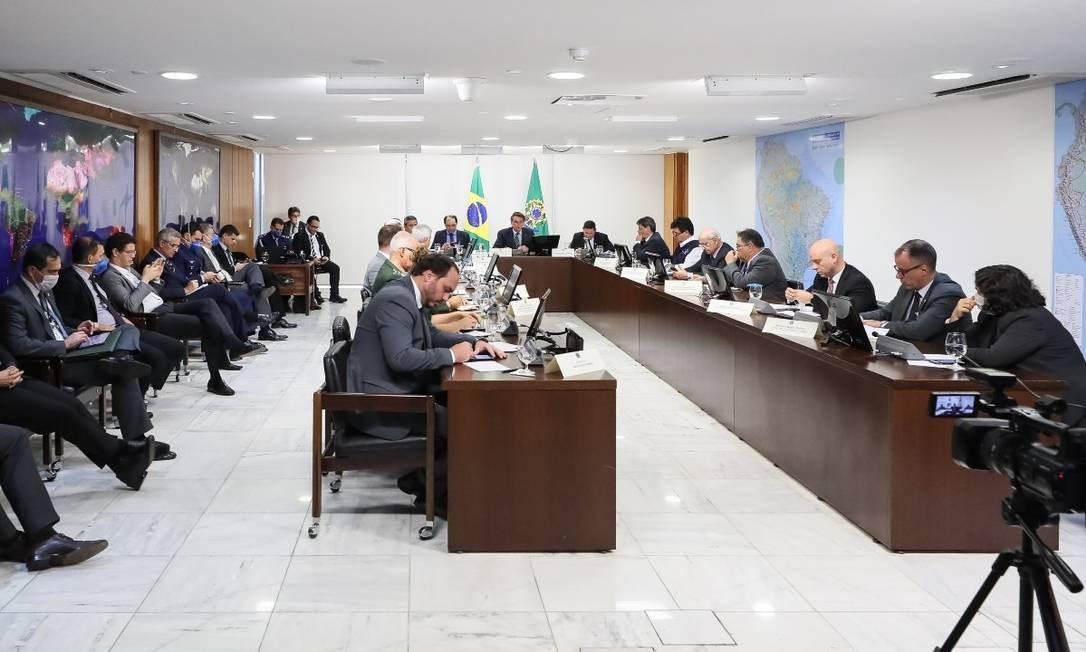 Carlos tem assento à mesa dos ministros, tirando o lugar de quem de fato é ministro, a exemplo de Ricardo Salles, sentado ao lado, mexendo no celular Foto: Isac Nóbrega/PR