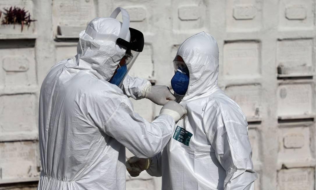 Sepultadores colocam equipamentos de segurança para fazerem o enterro de vítima com suspeita de Covid-19 Foto: FABIO MOTTA / Agência O Globo