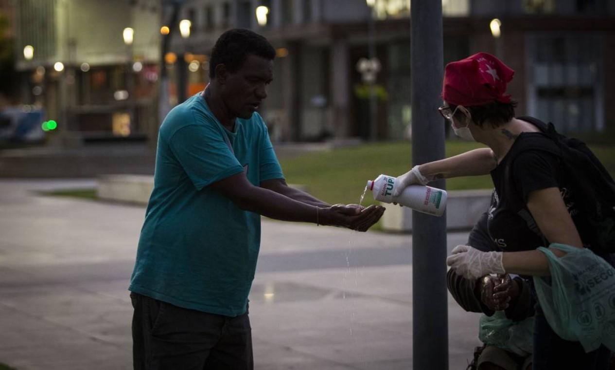 Voluntária ajuda homem em situação de rua a higienizar as mãos com álcool 70% Foto: Guito Moreto / Agência O Globo