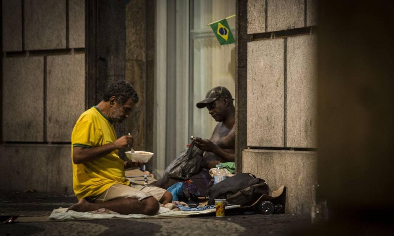Dois homens comem quentinha distribuída por voluntários no centro do Rio Foto: Guito Moreto / Agência O Globo