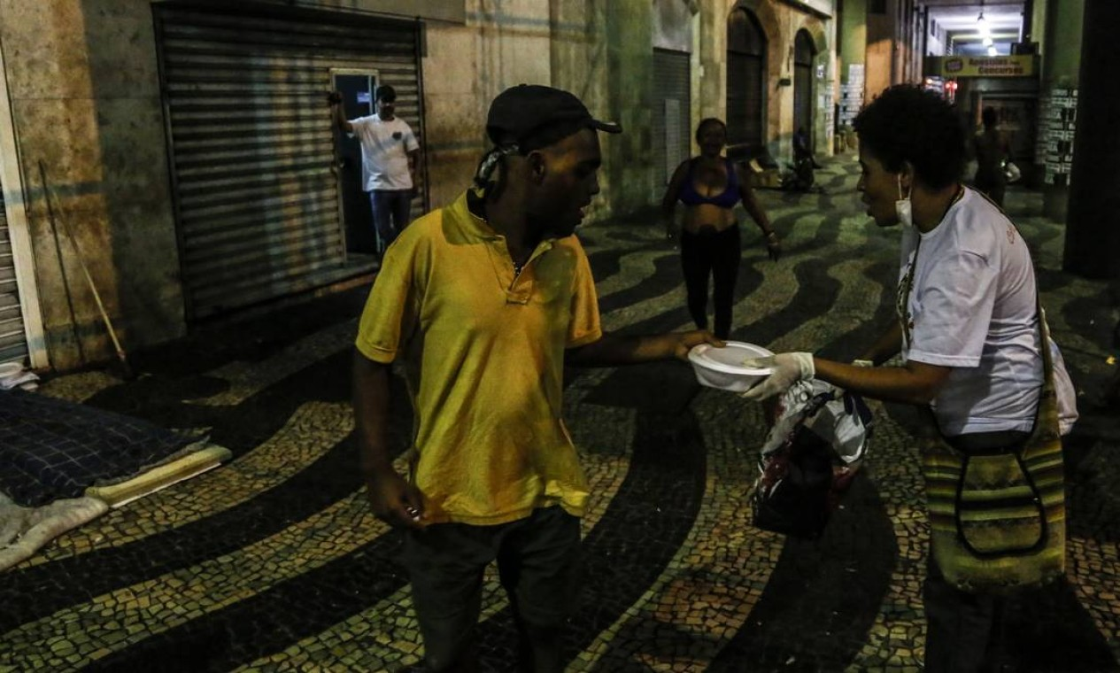 Voluntários distribuem alimentos e artigos de higiene pessoal para pessoas em situação de rua no centro do Rio Foto: Guito Moreto / Agência O Globo