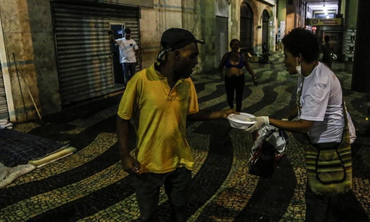Voluntários distribuem alimentos e artigos de higiene pessoal para pessoas em situação de rua no centro do Rio Foto: Guito Moreto / Agência O Globo - 01/04/2020