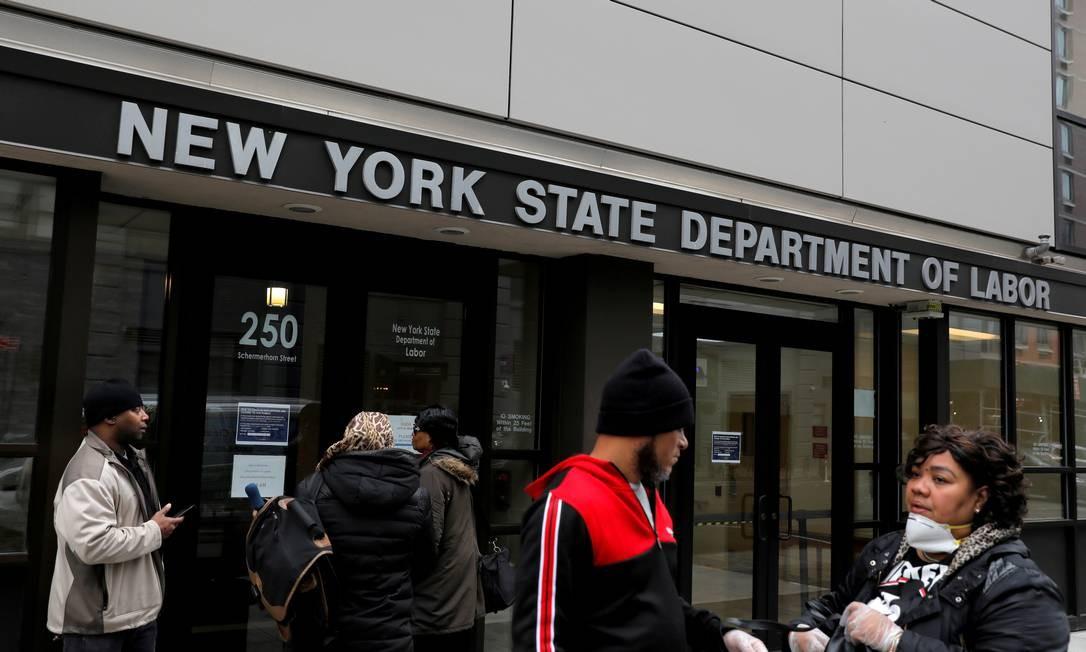 Pessoas se reúnem na entrada dos escritórios do Departamento de Trabalho do Estado de Nova York, que foram fechados ao público devido ao surto da covid-19 no bairro do Brooklyn Foto: Andrew Kelly / REUTERS