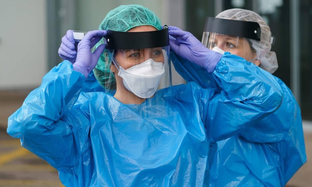 Na Espanha, funcionária da saúde põe equipamentos de proteção antes de entrar em emergência Foto: CESAR MANSO / AFP