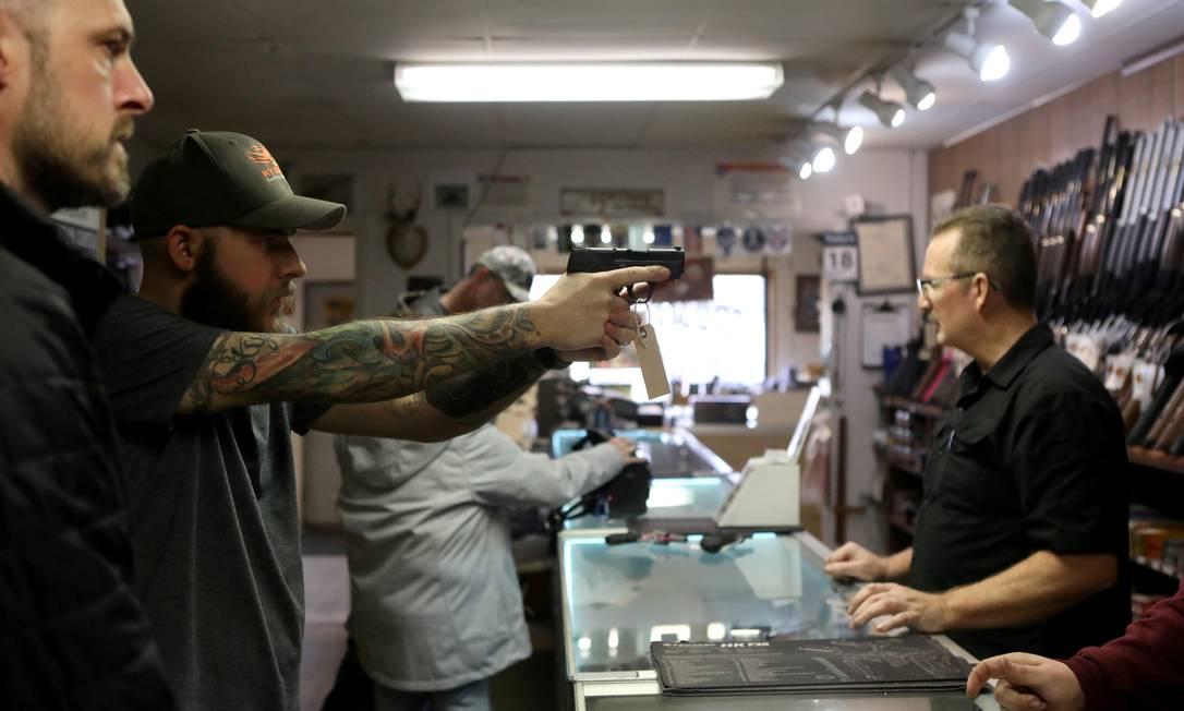 Homem experimenta arma semiautomática em uma loja nos EUA Foto: Jim Urquhart / REUTERS/18-03-2020