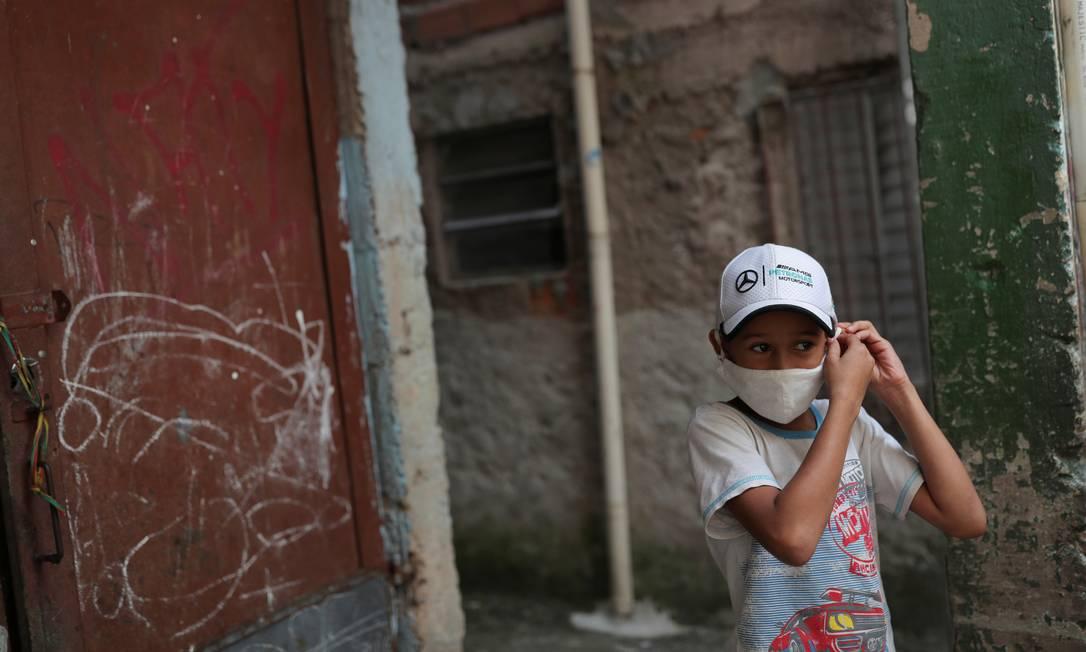 Criança ajusta máscara de proteção contra o coronavírus na favela de Paraisópolis, em São Paulo, uma das maiores do país Foto: AMANDA PEROBELLI / REUTERS