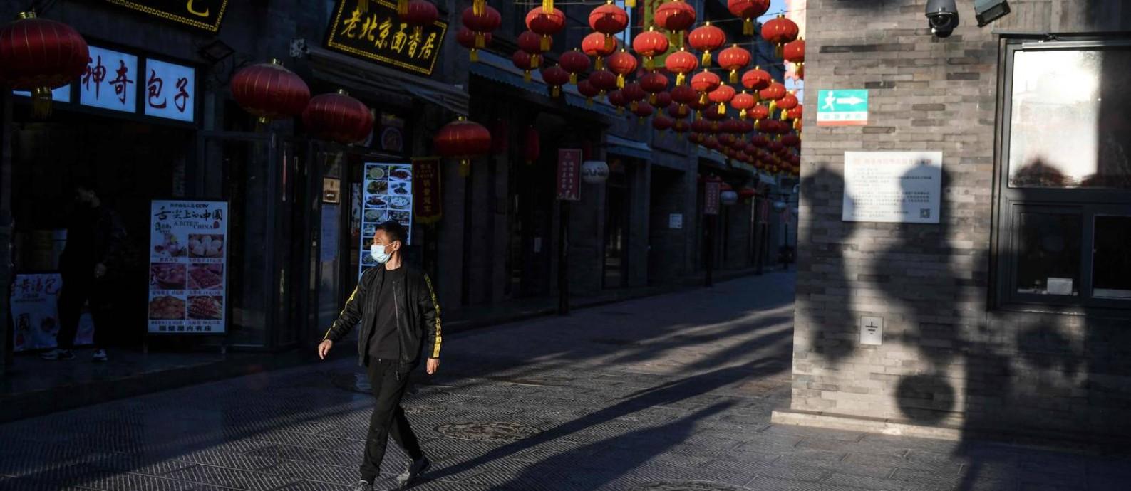 Um homem usando máscara como medida preventiva contra o coronavírus passeia em área turística de Pequim Foto: GREG BAKER / AFP