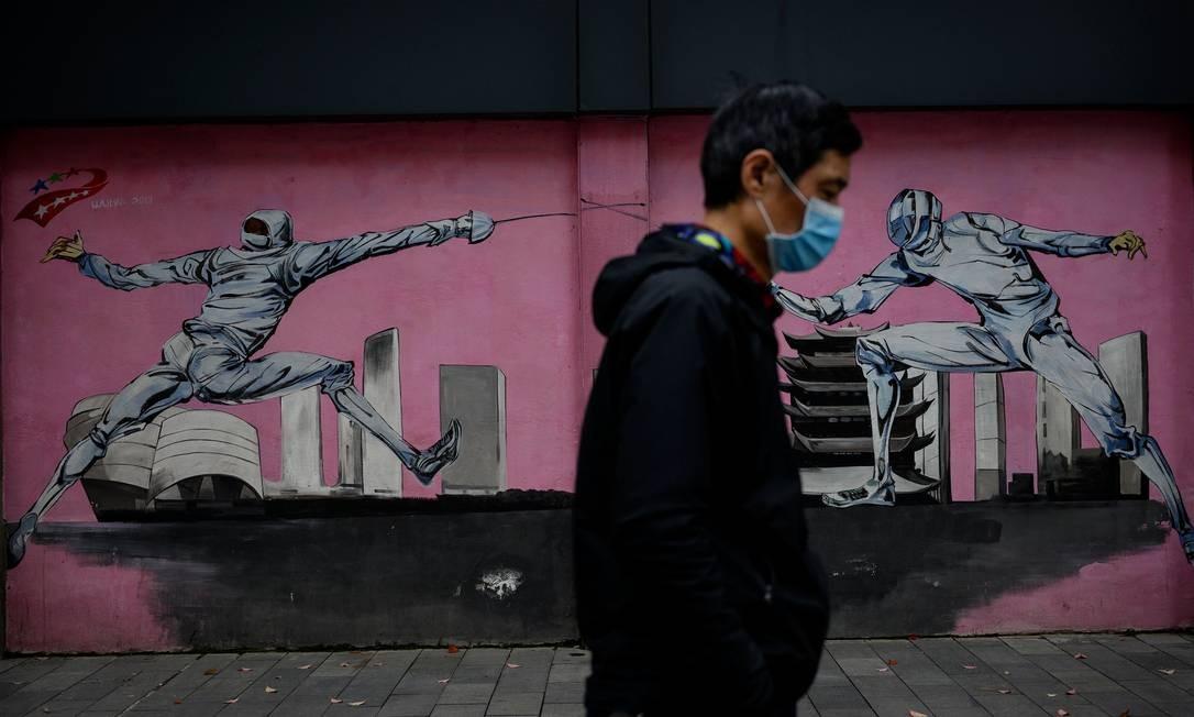 Homem com máscara facial caminha por Wuhan, na China Foto: NOEL CELIS / AFP
