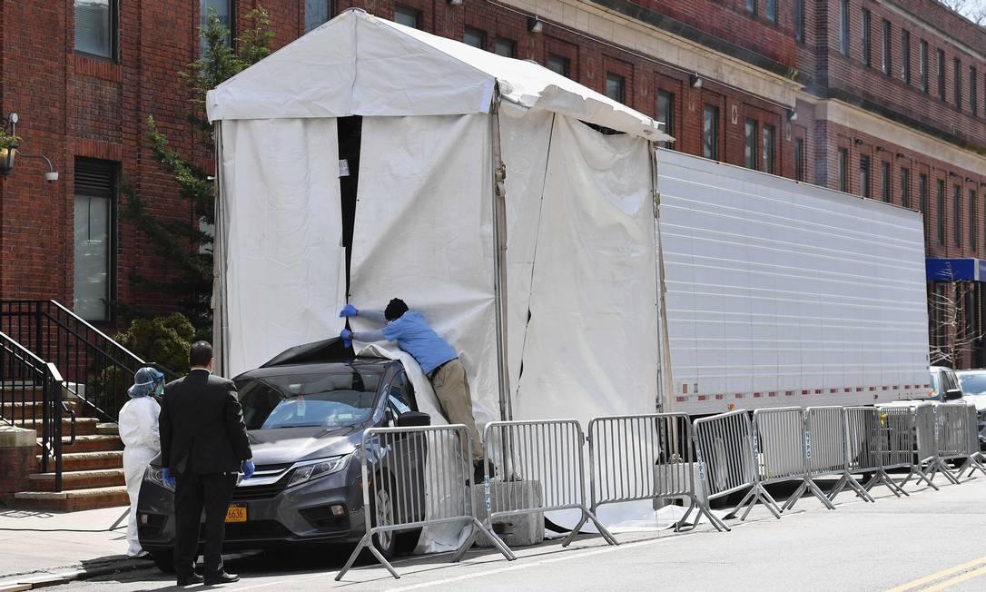 Carro de funerária perto de um caminhão refrigerado onde estão os corpos de algumas das vítimas da Covid-19 em Nova York Foto: ANGELA WEISS / AFP