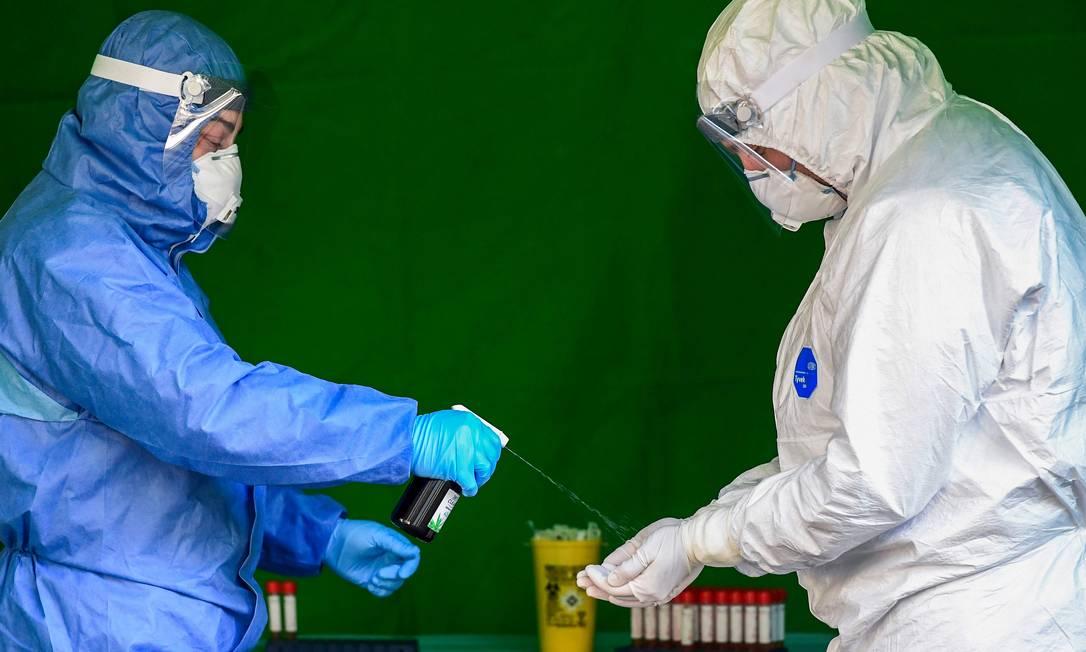 Profissionais de saúde desinfetam as luvas enquanto realizam testes para diagnosticar o coronavírus Foto: MIGUEL MEDINA / AFP