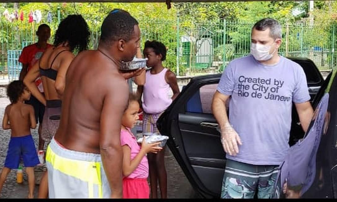 Pietro Cavalcante (à direita) ajuda na distrubuição de quentinhas no Méier Foto: Divulgação