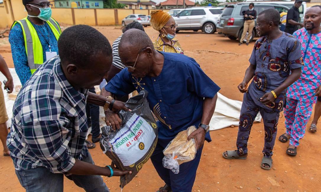 Cestas básicas são entregues na comunidade de Agbado e Oke-Odo LCDA, em Lagos. Desde segunda-feira, mais de 20 milhões de nigerianos entraram em confinamento na maior cidade da África-subsaariana Foto: IBEABUCHI BENSON UGOCHUKWU / AFP