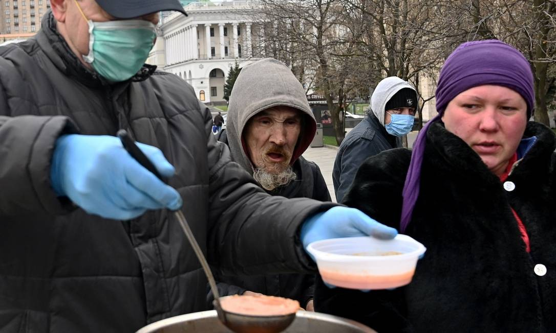 Trabalhador de caridade serve comida para pessoas sem-teto e vulneráveis na Praça da Independência, na capital ucraniana Kiev Foto: SERGEI SUPINSKY / AFP