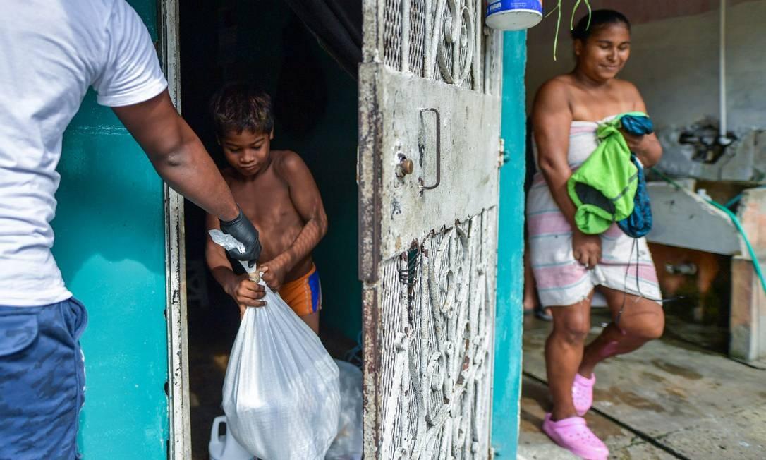 """Voluntário do """"Plano de Solidariedade do Panamá"""" entrega comida a famílias de baixa renda no bairro El Chorrillo, na Cidade do Panamá, como auxílio durante a pandemia do novo coronavírus Foto: LUIS ACOSTA / AFP"""