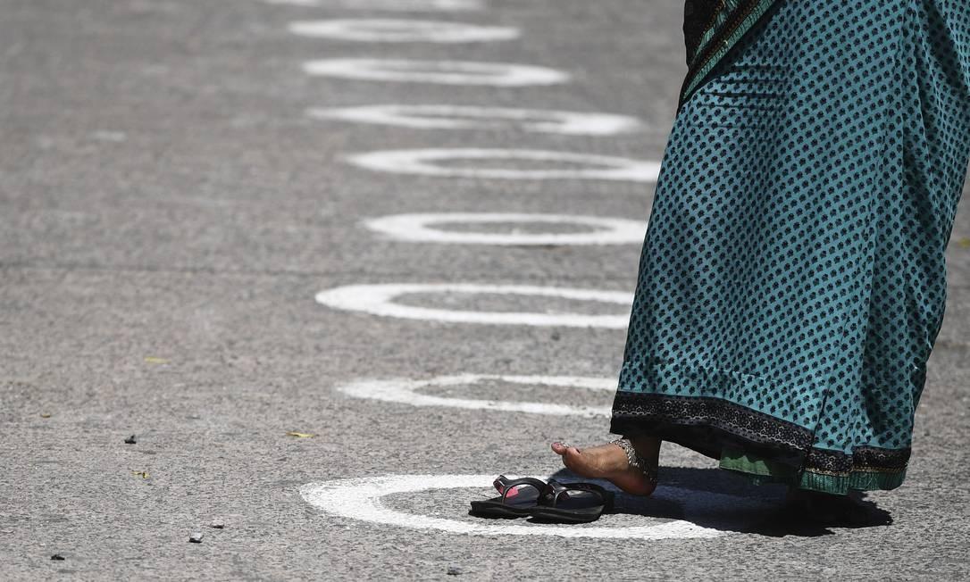 Mulher usa chinelos para marcar reservar o lugar marcado em fila distribuição gratuita de alimentos, organizados pelos Discípulos de Ramakrishna, grupo religioso hindu. As marcações no chão prezam pelo distanciamento de segurança para evitar o contágio do novo coronavírus Foto: SAJJAD HUSSAIN / AFP
