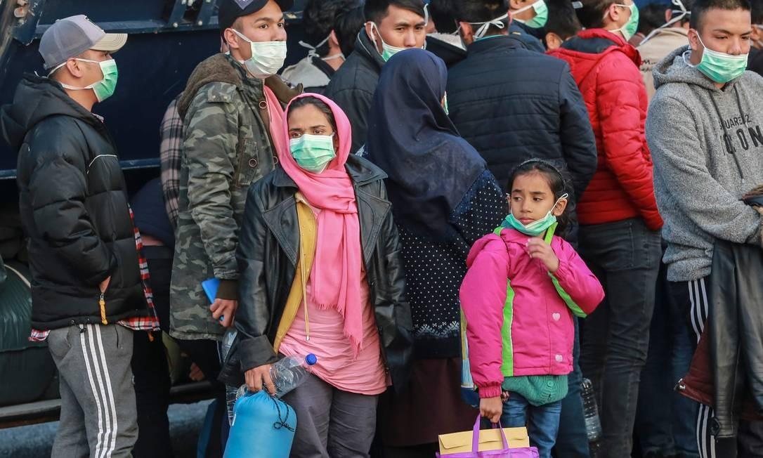Imigrantes chegam ao porto de Mitilene, na ilha grega de Lesbos, para serem transferidos para um campo fechado no norte da Grécia, enquanto o país luta para controlar o avanço do novo coronavírus Foto: MANOLIS LAGOUTARIS / AFP