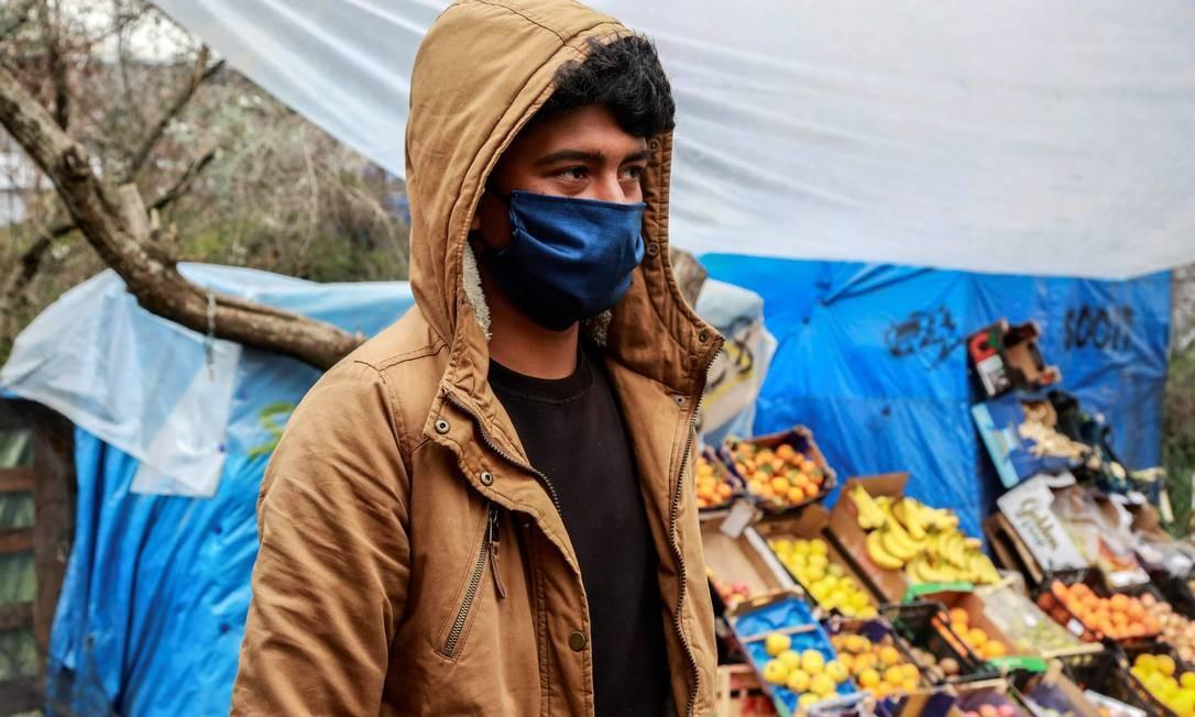 Imigrante usando máscara facial para medidas de proteção caminha por uma barraca de frutas e legumes em um acampamento improvisado próximo ao campo de Moria, na ilha grega de Lesbos, considerado o pior campo de refugiados do mundo, devido à superlotação Foto: MANOLIS LAGOUTARIS / AFP