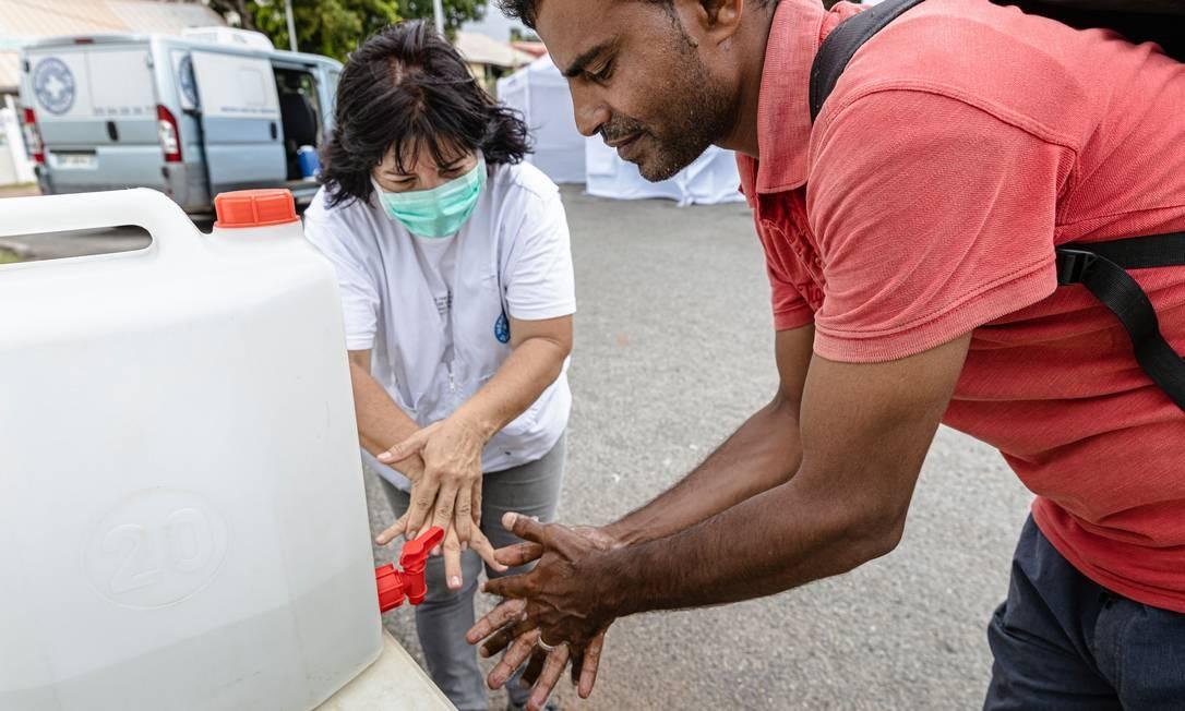 Equipe médica móvel da ONG Medecins du monde (Médicos do Mundo) ensina lavagem das mãos adequada para prevenção do contágio por coronavírus, na Place des Amandiers, em Cayenne, Guiana Francesa, onde cerca de 150 migrantes sírios estão hospedados no país Foto: JODY AMIET / AFP