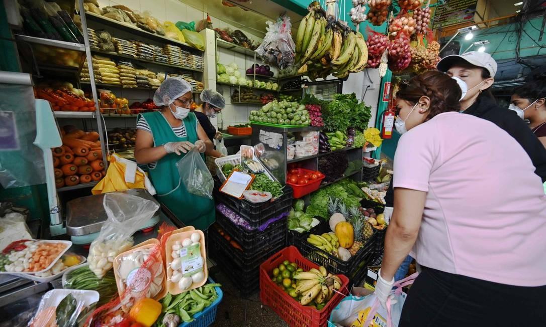 No Peru, mulheres fazem compras em quitanda de máscara Foto: CRIS BOURONCLE / AFP