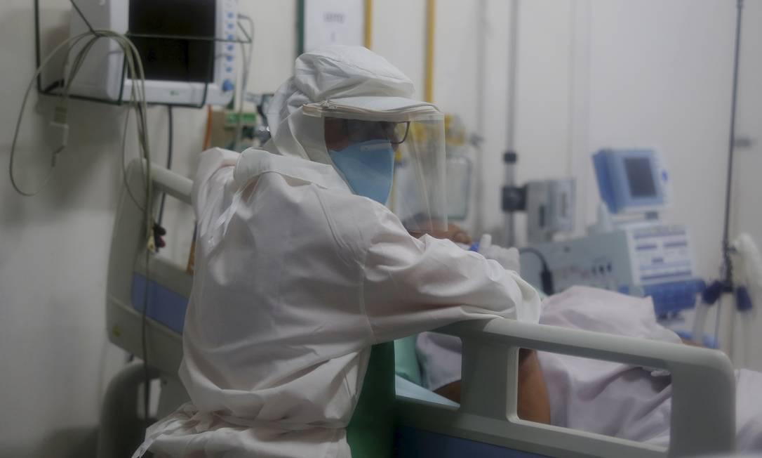 Paciente com sintomas do coronavírus é examinado por médico que usa equipamentos de proteção Foto: Fabiano Rocha / Agência O Globo