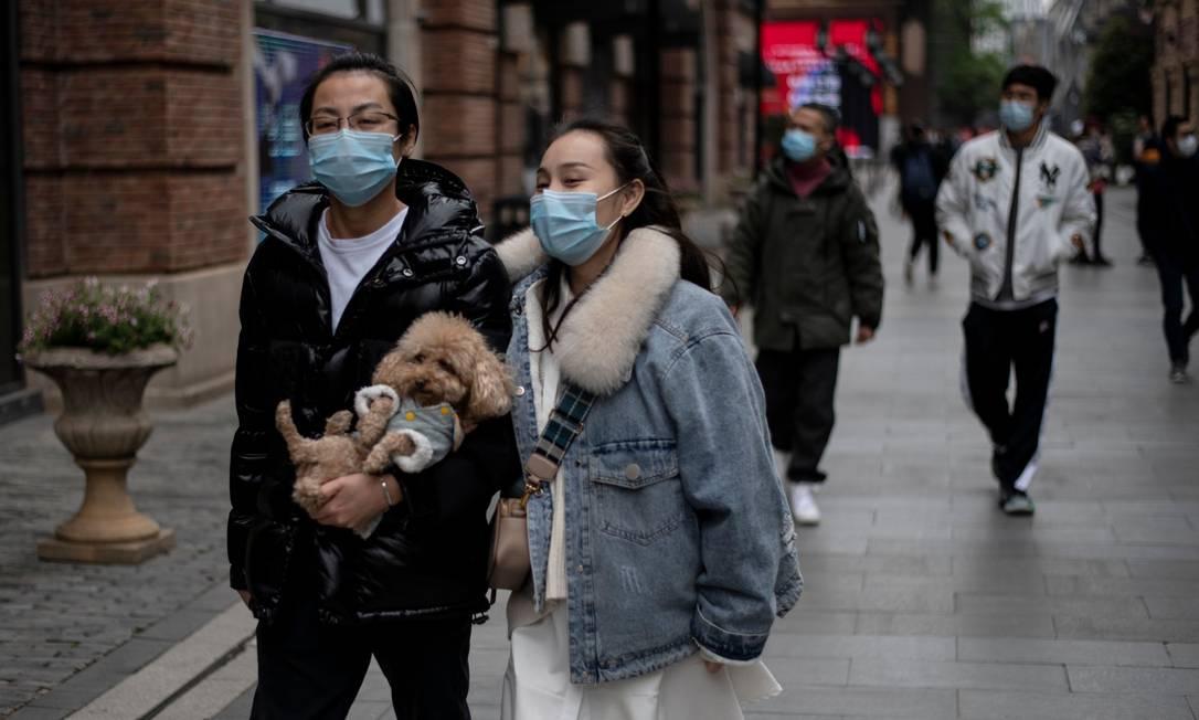 Pessoas andando pelas ruas de Wuhan, na China Foto: NOEL CELIS / AFP