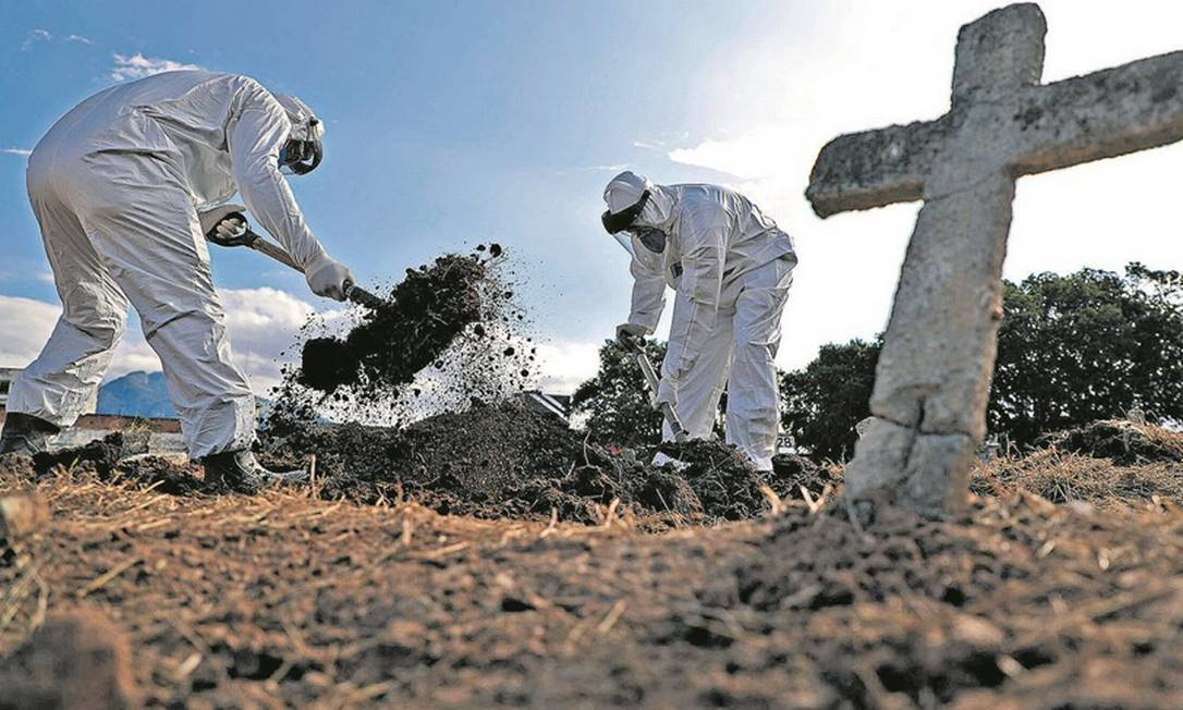 Coveiros do Cemitério do Caju usam equipamentos de proteção para enterrar um idoso que morreu de Covid-19 Foto: Fabio Motta / Agência O Globo