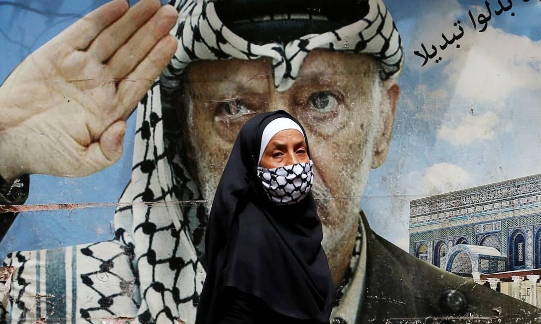 Mulher cobrindo o rosto com um keffiyeh, lenço símbolo da cultura palestina e tradicionalmente usando pelos homens, passa por um pôster do falecido líder palestino Yasser Arafat, no campo de refugiados palestinos de Shatila, durante surto da Covid-19, nos subúrbios de Beirute, Líbano Foto: MOHAMED AZAKIR / REUTERS