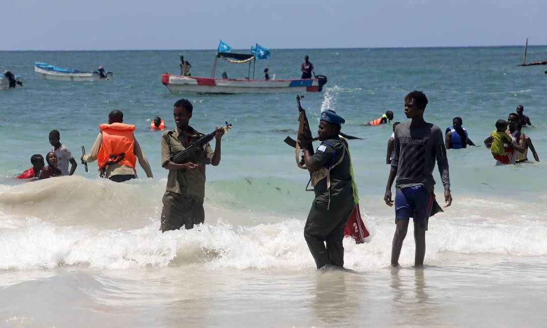 Um policial da Somália tenta dispersar foliões nadando no Oceano Índico, perto da praia do Lido, como parte de medidas para impedir a possível propagação de coronavírus Foto: FEISAL OMAR / REUTERS